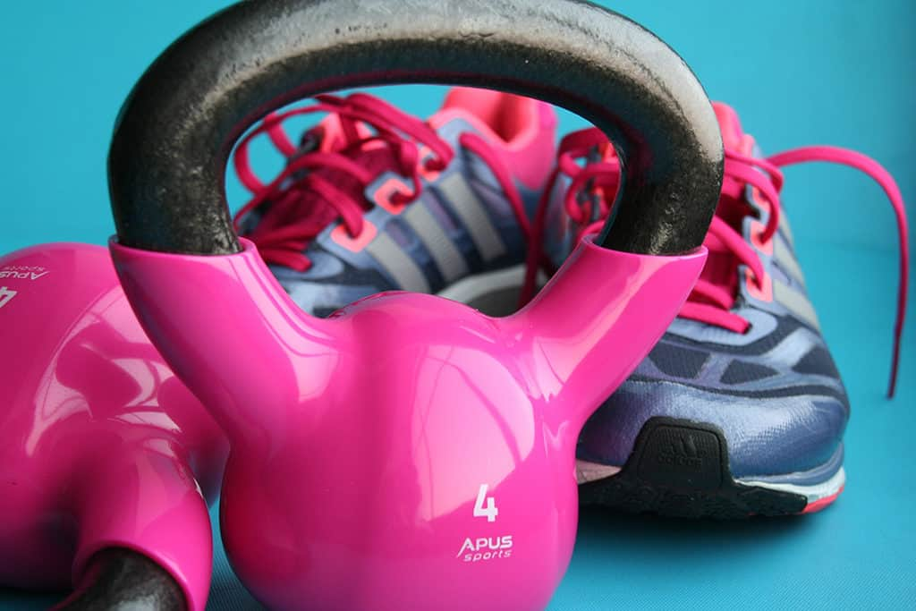A pair of sport shoes and pink dumbbells