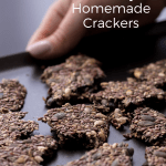A tray with homemade seed crackers holded by a hand