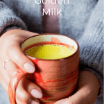 A mug with a yellow beverage called golden milk hold by two hands
