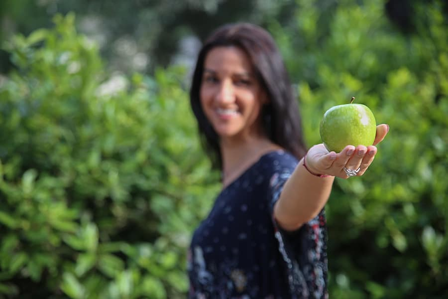 Claudia Canu holding a green apple