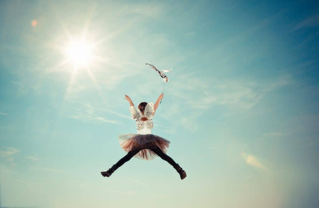 A girl with angel wings jumping