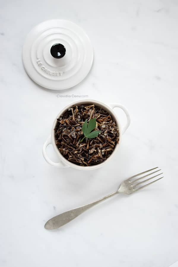 A white cocotte with black rice in it