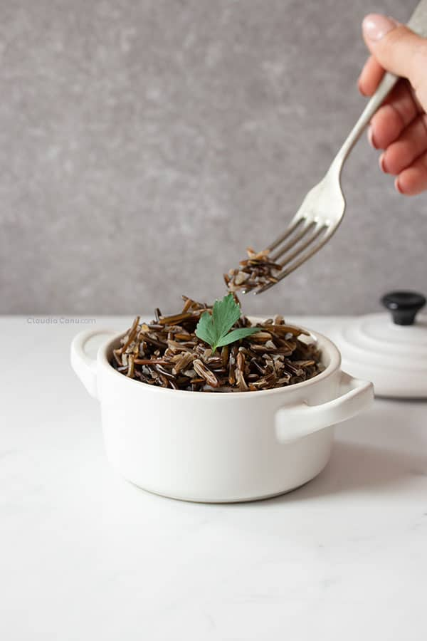 Wild rice in a white cocotte and a hand with a fork grabbing some