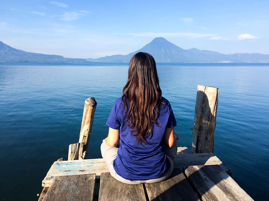 A woman meditating in front of a lake