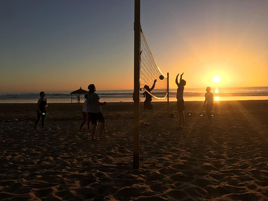 People playing beach volleyball during sunset