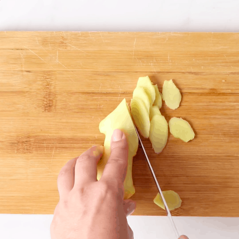 A hand cutting ginger